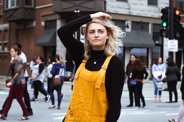 confused buy local shopper in yellow overalls on busy street
